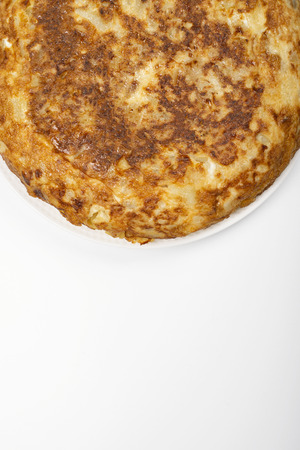 Omelette with potatoes on white background, isolated. Typical spanish food. Copy space.
