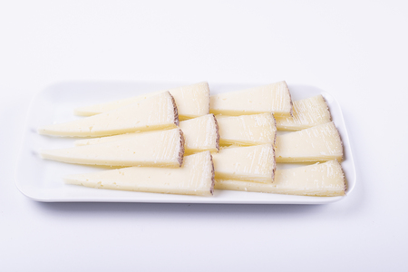Cheese cut on plate next to fork on white background. Isolated. Food