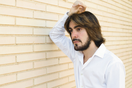Young, attractive man with a beard, is leaning against the wall with serious or sad face. Fashion