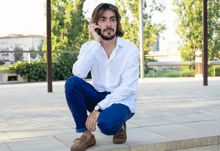 Attractive young man with beard, with white shirt talks to his smartphone with serious face. Fashion