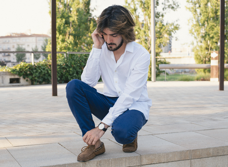 Attractive young man with beard, with white shirt talks to his smartphone. Fashion