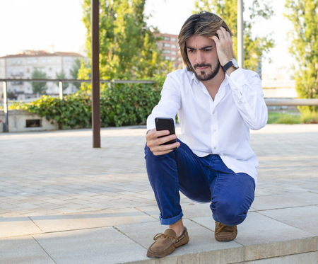 Attractive young man with beard, wearing white shirt looks at his smartphone worried in the park. Fashion