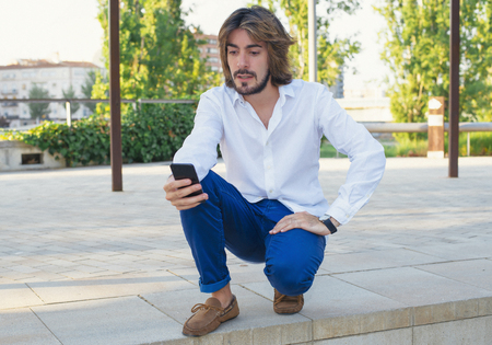 Attractive young man with beard, with white shirt looks at his smartphone with serious face in the park. Fashion