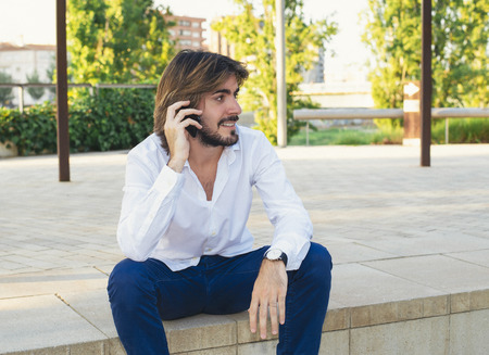 Attractive young man with beard, with white shirt who is in the park smiles while talking on the smartphone. Fashion