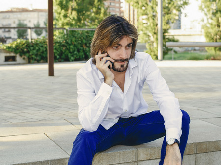 Attractive young man with beard, with white shirt talks to a smartphone sitting in the park. Fashion Stock Photo