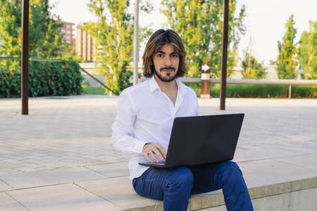 Attractive young man with beard uses the laptop and looks at the camera. Fashion Stock Photo