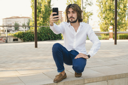 Attractive young man with beard, with white shirt makes himself a selfie with serious face in the park. Fashion Stock Photo