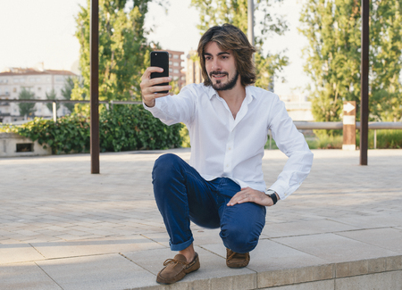 Attractive young man with beard, with white shirt makes himself a selfie in the park. Fashion Stock Photo