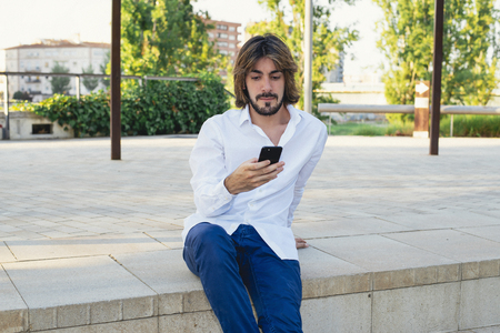 Attractive young man with beard, with white shirt looks at his smartphone in the park. Fashion