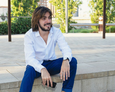 Attractive young man with beard, with white shirt holds a smartphone in his hand and is in the park, smiles. Fashion