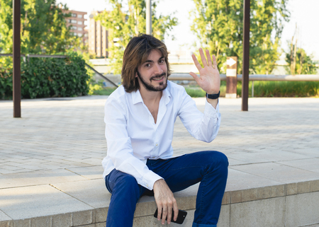 Attractive young man with beard, with white shirt holds a smartphone in his hand and is in the park, smiles and waves at the camera. Fashion