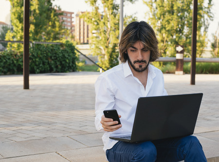 Attractive young man with beard looks at his smartphone while having on his legs a laptop. Fashion