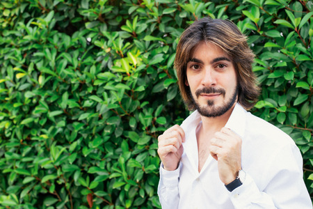 Attractive young man with beard, with white shirt and with green leaves in the background smiles looking at the camera. Fashion Stock Photo