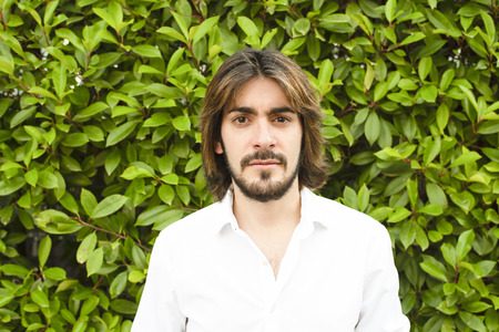Young man with beard and long hair with white shirt and with green leaves looks with serious face at the camera. Stock Photo