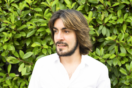 Profile portrait of young man with beard and long hair wearing white shirt and with green leaves. Stock Photo