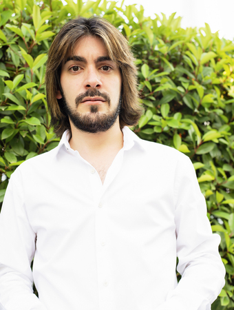 Half-length portrait of attractive young man with beard and long hair dressed in white shirt looks with serious face at the camera. Stock Photo
