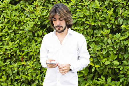 Young man with beard, long hair, white shirt with green leaves in the background, looks at his smartphone. Technology.
