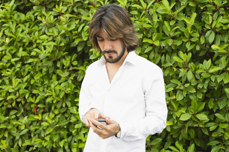 Young man with a beard, long hair, white shirt with green leaves in the background, surf the Internet with your smartphone. Technology.