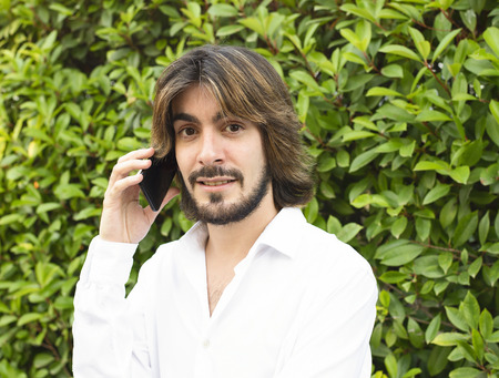 Young man with a beard, long hair, white shirt with green leaves in the background, talks to his smartphone and smiles at the camera. Stock Photo