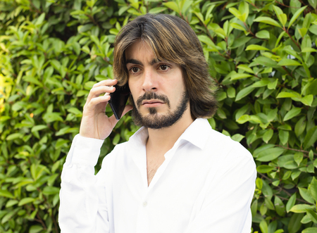 Young man with a beard, long hair, white shirt with green leaves in the background, speaks with his smartphone with an angry face.