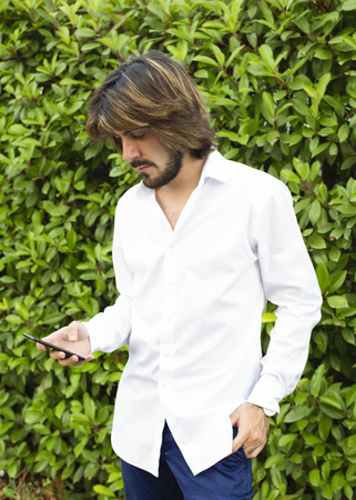 Vertical shoot of an attractive young man with white shirt, blue pants, with plants and green leaves behind, who is looking at his smartphone. Technology. Banque d'images - 112627414