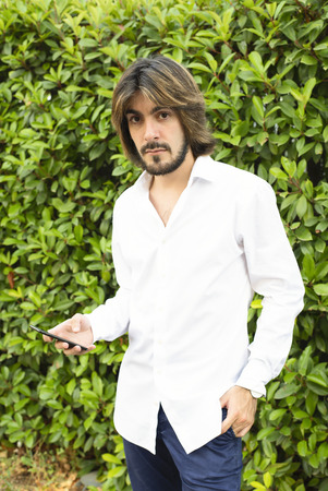 Young man with beard, long hair, white shirt with green leaves in the background, talks to his smartphone looks at the camera with an angry face.