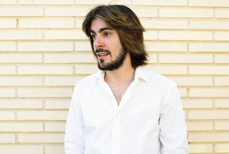 Young man with a beard, long hair, white shirt, with parede in the background smiles looking to the side. Stock Photo