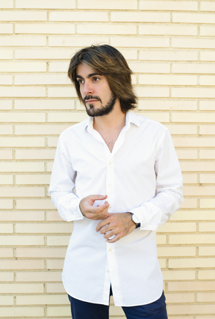 Vertical half-length shoot young man with beard, long hair, white shirt, blue pants, with wall in the background looks at the camera with serious face.