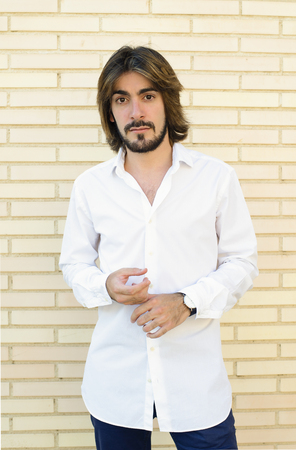 Vertical half-length shoot young man with beard, long hair, white shirt, blue pants, with background in the background looks at the camera with a serious face. Stock Photo
