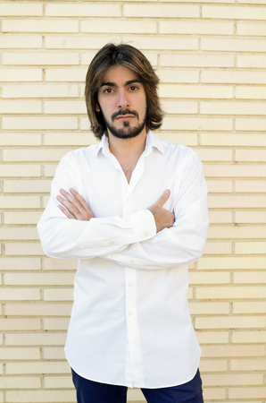 Vertical shoot of attractive young man with long hair, beard, with crossed arms, white shirt, blue pants with a wall behind looks with serious face at the camera.