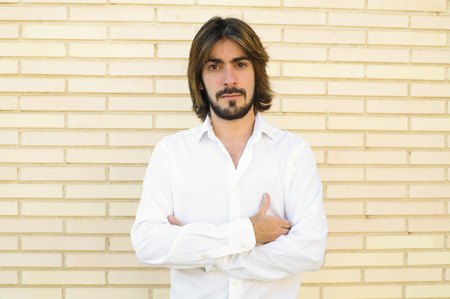 Horizontal shoot of attractive young man with long hair, beard, with crossed arms, white shirt, blue pants with a wall behind looks with serious face at the camera.