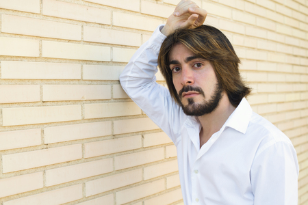 Horizontal shoot of attractive young man with long hair, beard, white shirt, leaning on the wall looks with serious face at the camera.