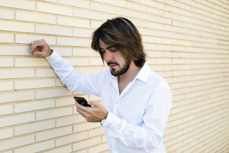 Horizontal shoot of attractive young man with long hair, beard, white shirt, leaning on the wall looks at his smartphone. Copy space. Stock Photo