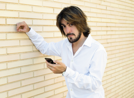 Horizontal shoot of attractive young man with long hair, beard, white shirt, leaning against the wall holds a smartphone in his hand and looks at the camera. Copy space.