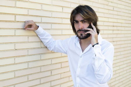 Horizontal shoot of attractive young man with long hair, beard, white shirt, leaning against the wall speaks through his smartphone looks angrily at the camera. Copy space.