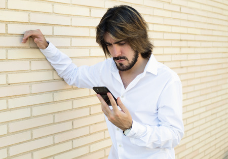 Horizontal shoot of attractive young man with long hair, beard, white shirt, leaning against the wall looks angry at his smartphone. Copy space.