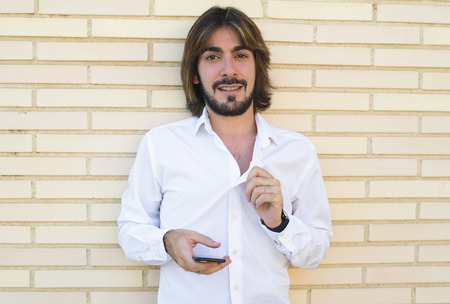 Horizontal shoot of attractive young man with long hair, beard, white shirt, leaning against the wall and with a smartphone in his hand looks at the camera smiling. Copy space. Technology.