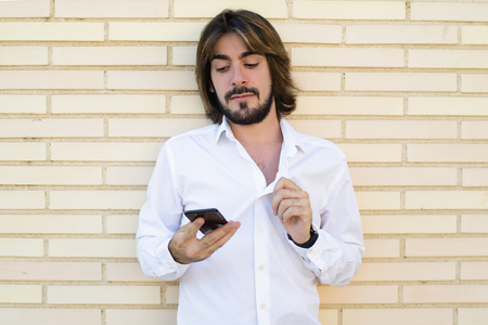 Horizontal shoot of attractive young man with long hair, beard, white shirt, leaning against the wall and looking at his smartphone. Copy space. Technology. Stock Photo