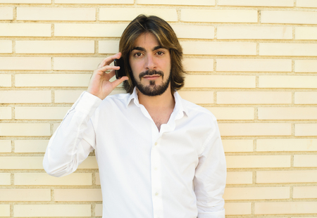 Horizontal shoot of attractive young man with long hair, beard, white shirt, leaning against the wall speaks through his smartphone while looking smiling at the camera. Copy space.