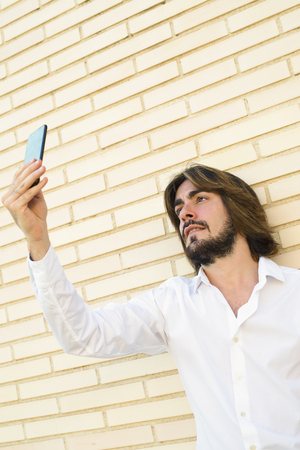 Vertical shoot of attractive young man with long hair, beard, white shirt, leaning on the wall makes a selfie with his smartphone. Copy space. Technology