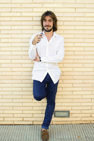 Vertical shoot of attractive young man with long hair, beard, white shirt, blue pants leaning on the wall looking smiling at the camera. Copy space. Technology.