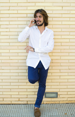 Vertical shoot of attractive young man with long hair, beard, white shirt, blue pants leaning on the wall speaks through his smartphone. Copy space. Technology.