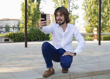 Horizontal shoot of attractive young man with long hair, beard, white shirt, blue pants makes a selfie with his smartphone. Copy space. Technology.