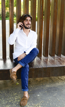 Vertical shoot of attractive young man with long hair, beard, white shirt, sitting on a wooden bench smiles while talking with his smartphone. Technology Stock Photo