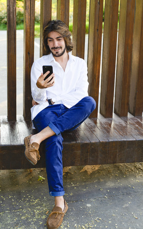 Vertical shoot of attractive young man with long hair, beard, white shirt and blue pants is sitting on a wooden bench and smiles while looking at his smarthpone. Coy space. Video conference