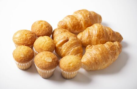 Croissants and cupcakes on white background. Banco de Imagens