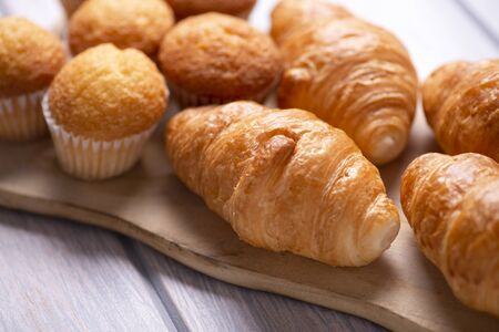Close-up of cupcakes and croissants prepared for breakfast on wooden board on white wooden table. Banco de Imagens