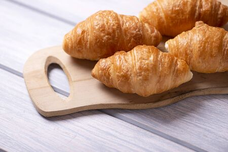 Close-up of croissants prepared for breakfast on wooden board on white wooden table. Banco de Imagens