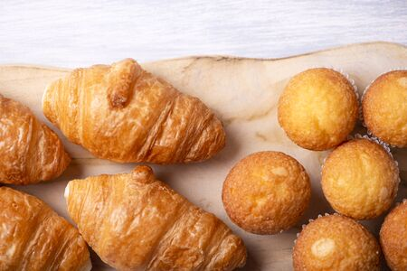 View from above of cupcakes and croissants prepared for breakfast on wooden board on white wooden table. Banco de Imagens