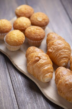 Cupcakes and croissants fresh out of the oven on wooden board.